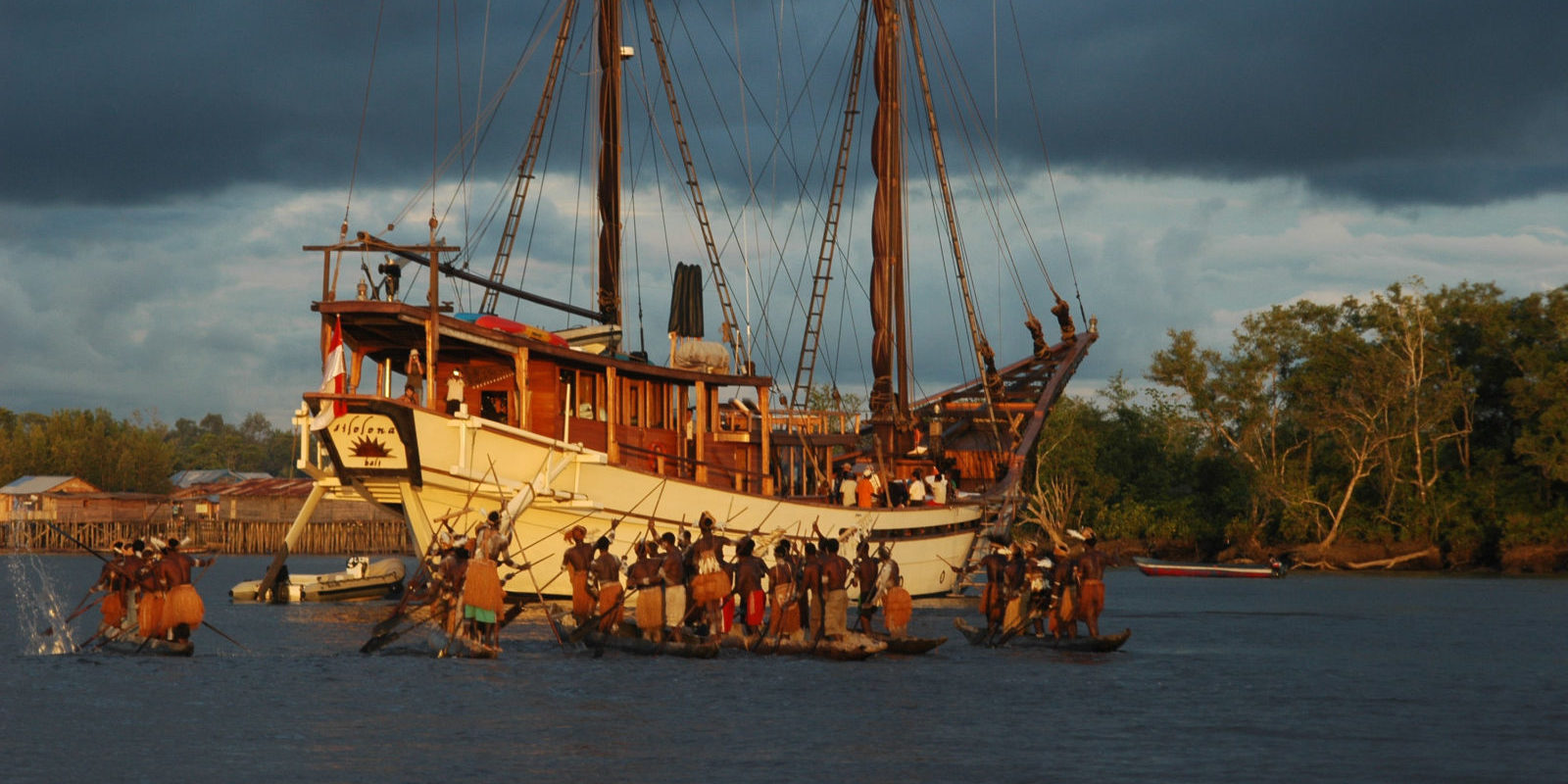 Papua, Asmat regency; a fleet of Asmat canoes with warriors in traditional dress  greets Silolona on arrival at Syuru village, Agats