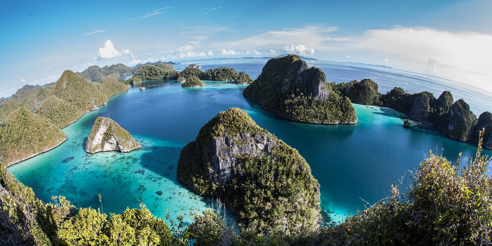 A gorgeous lagoon is surrounded by limestone islands in Wayag, Raja Ampat, Indonesia. This beautiful area is known for its high marine biodiversity and excellent scuba diving and snorkeling.